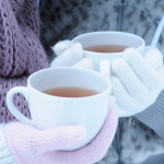 BP6MN6 Close-up of two young women holding hot tea on winter day